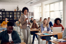Happy African American Professor Teaches Group Of College Students In Classroom.