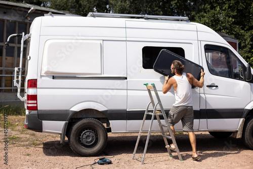 Obraz na plátně Camper van conversion - Man installing a side window