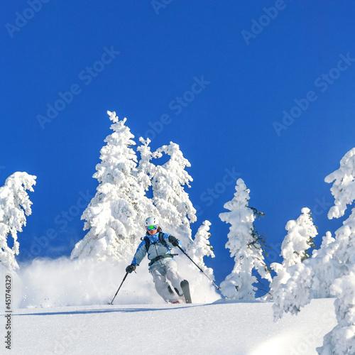 Freeriderin im Telemark-Stil bei einer Abfahrt in herrlicher Winterlandschaft