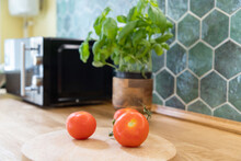 Fresh Tomatoes And Basil In Modern Kitchen Interior With White Furniture Home Background