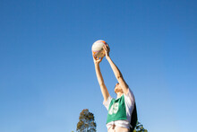 Horizontal Shot Of A Young Woman Holding A Ball Up High In The Air On A Sunny Day With Clear Skies