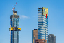 Horizontal Shot Of Two High Rise Building, One Under Construction In Front Of A Clear Blue Sky