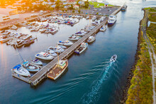 Aerial View Of A Marina At Sunset With A Small Runabout Leaving A Wake Through An Access Channel