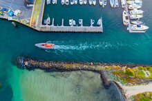 Aerial View Of A Power Boat Leaving A Boat Marina Between A Jetty And A Break Water