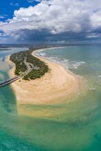 Aerial View Of A Coastal Sand Beach Around A Narrow Strip Of Land With Rain Clouds Overhead
