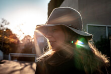 Close Up Shot Of Woman With Eyes Closed Wearing A Hat And A House And Sunlight In The Background