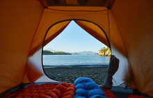 Camping With Tent At Beach Of Mediterranean Sea, Two Tourists People Lying In Sleeping Bag With View On Seashore