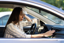 Exhausted Young Woman Suffering From Heat Inside Car With Broken Air Conditioner. Female Driver Feeling Sick And Headache From Hot Air Temperature In Vehicle Regulating Condition Panel Knobs In Summer