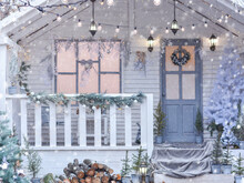 Winter View Of A Country House With Christmas Decorations. Snowy Courtyard With Christmas Porch, Veranda, Wreath, Christmas Tree, Firewood, Garland. Merry Christmas And Happy New Year
