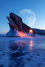 Winter Siberian Landscape. Lake Baikal, Silhouette Of A Man With A Torch On The Background Of The Rock And The Moon. Lake Baikal.