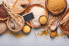 White, Brown And Red Rice, Buckwheat, Millet, Corn Groats, Quinoa And Bulgur In Wooden Bowls On The Light Gray Kitchen Table. Gluten-free Cereals. Top View With Copyspace