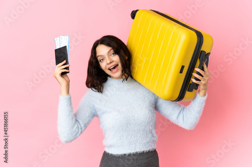 Teenager Ukrainian girl isolated on pink background in vacation with suitcase and passport