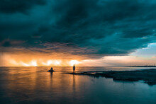 Person Standing On The Shore Surrounded By The Sea Under A Stormy Sky During A Breathtaking Sunset
