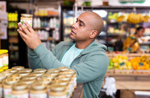 Focused Hispanic Man Choosing Necessary Foodstuffs In Grocery Store, Reading Product Contents On Jar