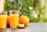 Fototapeta Kawa jest smaczna - Glasses of tasty orange juice on table outdoors, closeup