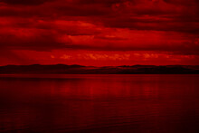 The Surface And The Island Of Red Water Scenery. Sky With Clouds. Bloody Sunset Background With Copy Space For Design. War, Apocalypse, Armageddon, Nightmare, Halloween, Evil, Horror Concept.
