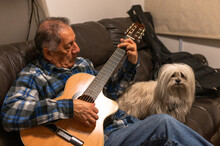 Old Man Playing Acoustic Guitar And Sitting On Sofa With Little White Dog.