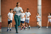 Physical Education Teacher And Group Of Elementary Students Run While Warming Up At School Gym.