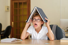 Funny Schoolchild In Glasses Making Face While Sitting With Book On Head At Table In Classroom
