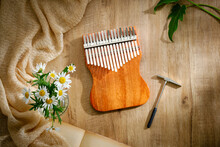 Kalimba And Hammer For Tuning Kalimba Isolated On Wooden Background. Concept Vintage.