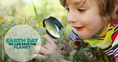 Composition of earth day logo and text over boy using magnifying glass