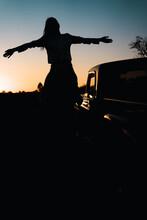 Silhouette Of Couple Near Car Against Sunset Sky