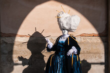 Female Wearing A Mask And Blue Carnival Costume Standing By The Wall In Venice, Italy