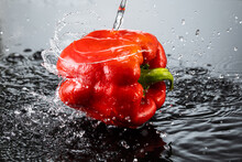 Bell Peppers On A Dark Gray Background With Splashes Of Water