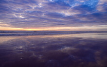 Waves Rolling In At Sunrise Onto Wet Sand Reflecting Colourful Clouds In The Sky
