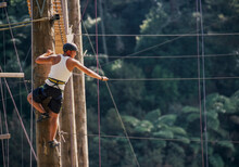Man Standing At Top Of Poll Ready To Balance On Suspended Rope At Outdoor Ropes Course