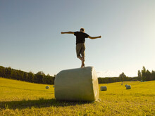 Back View Of Boy Boy Balancing On Round Haybale In Field