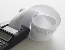 Calculator Sitting On Desk With Printed Tape Full Of Numbers
