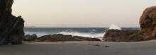 Looking Between Large Rocks With Waves Crashing - Surfers Paradise Skyline On The Horizon