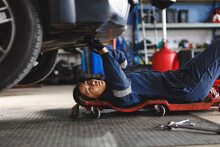 Mixed Race Female Car Mechanic Wearing Overalls, Lying On A Board, Checking Car