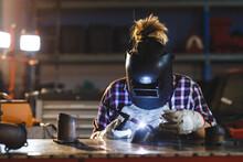 Mixed Race Female Car Mechanic Welding Car Part In Workshop