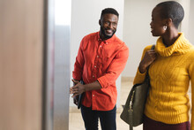 Smiling African American Male And Female Creative Colleagues Talking At Elevator