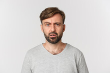 Close-up Of Handsome Confused Guy Cant Understand Something, Frowning And Looking Perplexed, Standing Over White Background