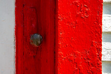 A Closeup Of An Antique Rusty Iron Decorative Metal Door Handle On A Brightly Painted Vibrant Red Wooden Door.  The Vintage Door Is Next To A White Wall And Glass Window That's Paint Is Peeling.