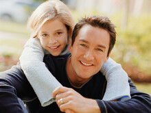 Daughter With Arms Wrapped Around Fathers Shoulders Sitting On Front Lawn Of Home