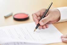 契約書にサインをする高齢者の手元