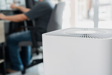 Close Up Air Purifier In The Room Is Very Safe And Clean To Breathe With Filter Dust PM 2.5 And A Man Use Computer Desktop Working In Home In Clean Air