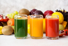 Glasses With Healthy Juice, Fruits And Vegetables On Light Background
