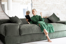 Stylish Woman In Green Dress Using Digital Tablet While Sitting Relaxed On The Comfortable Sofa At Home. Leisure Time With A Digital Device Or Working Home Concept