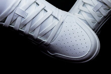 Pair Of White Sneakers On A Black Background