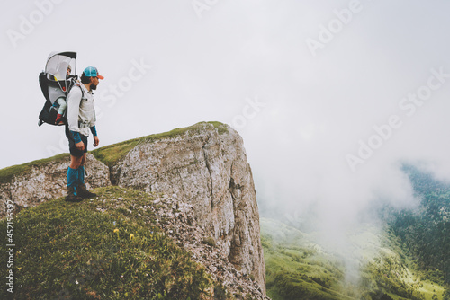 Man father hiking with child in backpack family vacations travel together in foggy mountains healthy lifestyle adventure trip outdoor