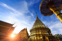 Golden Pagoda And Building In Sunlight And Blue Sky With Clouds In The Ancient Temple At The North Of Thailand, Wat Phra That Doi Suthep, One Of The Most Famous Places In Thailand For Tourism