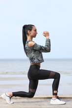 Young Woman Exercising In The Morning By The Sea