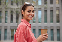 Positive Dark Haired Woman In Stylish Red Shirt Sunglasses On Head Strolls In Unknown City Drinks Coffee From Paper Cup Enjoys Leisure Time Smiles Broadly Poses Against Blurred Building Background