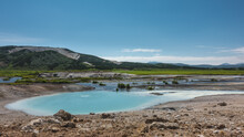 An Amazing Turquoise Geothermal Lake In The Caldera Of An Extinct Volcano. There Is Almost No Vegetation On The Stony Soil. A Mountain Range Against The Blue Sky. A Summer Day. Kamchatka. Uzon