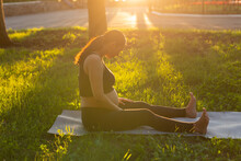 Pregnant Woman Sitting On Yoga Mat In Summer Park. Healthy Lifestyle, Expecting Baby And Childbearing Concept.